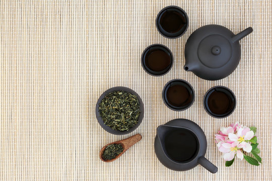 Japanese sencha sukiygu makoto tea with teapot, leaves and cups with blossom on bamboo background with copy space.