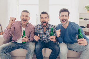 Close up portrait of attractive, stylish, cheerful guys yelling goal with wide open mouths, holding bottles with lager in hands, watching soccer word cup competition, cheering for favorite team