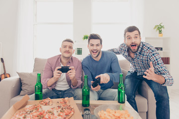 Portrait of stylish attractive funny modern successful three men in casual outfits playing video game holding joystick in hands, having snack, chips, good, alcohol beverages on the table
