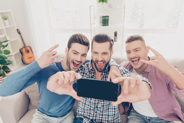 Portrait of cool, crazy, funky, funny, attractive, stylish lovers, fans, shouting screaming gesturing with fingers rock and roll sign shooting selfie on smart phone sitting in living room