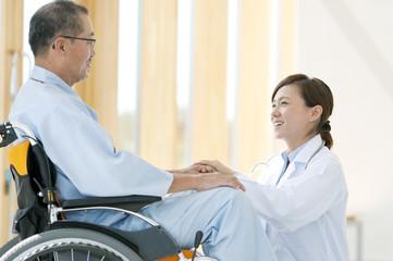 患者の手を握る女医