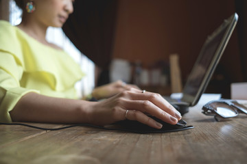 Close up of a woman hands working with a laptop and a mouse in a home interior or on desk wood beside window light shade