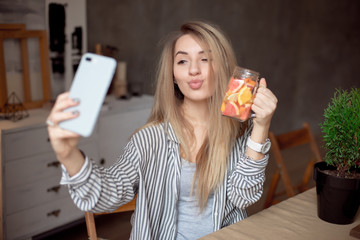 Pretty young caucasian girl taking selfie with glass of fresh lemonade indoor.