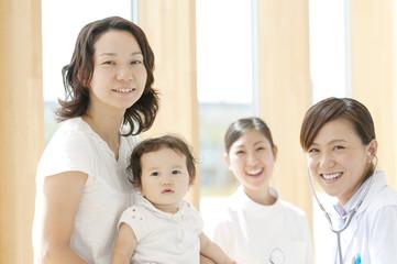 赤ちゃんを抱く母親と女医と看護師