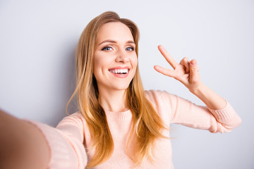 Close up portrait of cheerful excited rejoicing joyful cute beautiful with beaming shiny smile lady having fun taking selfie using smartphone front camera showing v-sign isolated on gray background