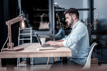 Comeback to work. Busy smart confident employee sitting on his workplace by the table using the laptop and concentrating on his task.