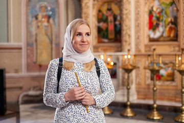 Caucasian woman holding candle in orthodox church