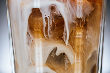 close up view of cold iced coffee with milk in glass