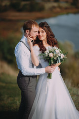 wedding. stylish groom with a beard and a beautiful bride on background of the river. rustic style. boho.