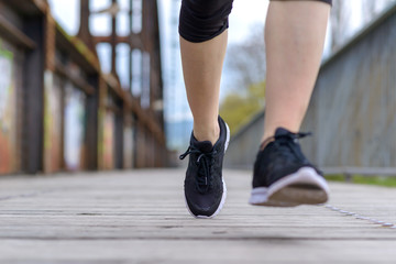 Sporty woman running on an old boardwalk bridge