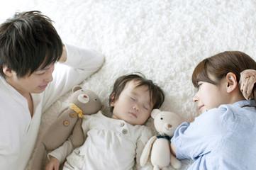 赤ちゃんの寝顔を見守る夫婦