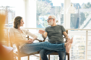 Relaxed mature couple talking on chairs at home