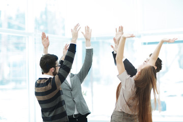 Motivated young business team pledging support raising their hands