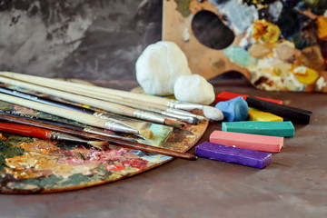 Palette with paints, colored clay and clay for modeling. School of Art.