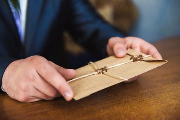Man hand hold envelope on the wooden background. Brown envelope