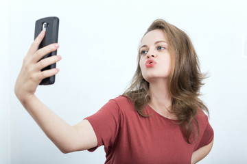 Young caucasian woman taking selfie with air kiss