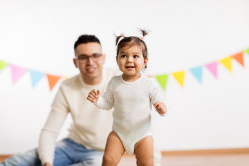 family, holidays and people concept - happy father and little daughter on birthday party