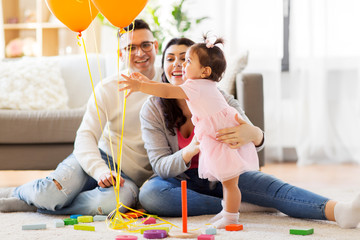 family, holidays and people concept - happy mother, father and little daughter reaching to balloons at home birthday party