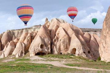 Colorful hot air balloons flying over Red valley in Cappadocia, Anatolia, Turkey