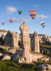 Colorful hot air balloons flying over unique geological formations in Cappadocia, Anatolia, Turkey