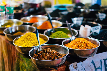 Indian spices in shiny metal bowls put for sale on a vendors table