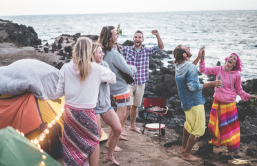 Happy friends dancing and making barbecue beach party