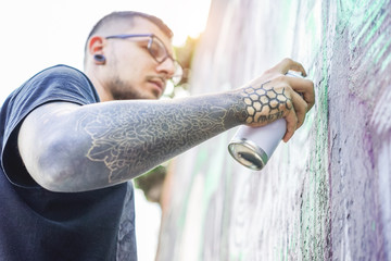 Tattooed graffiti artist painting with color aerosol on the wall