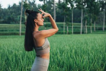 brünette Frau macht Yoga im Reisfeld