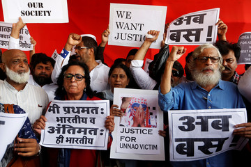 People shout slogans and hold placards during protest against recent rapes, in Mumbai