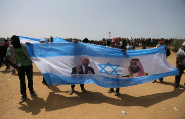 Palestinian demonstrators hold a representation of an Israeli flag with pictures of Trump and bin Salman before burning it during a protest demanding the right to return to their homeland, at the Israel-Gaza border, in the southern Gaza Strip
