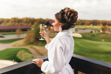 Elegant bride in bathrobe holding wineglass. Wedding, preparation.