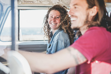 Happy couple inside minivan doing a adventure road trip