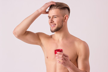 Studio shot of young naked man applying gel on his hair and smiling while standing isolated on white background. Handsome sexy hipster making stylish hair style. Men's hair care and hair style concept