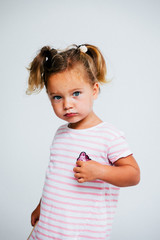 Portrait of a little girl standing against white background