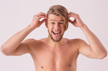 Funny shirtless young man trying to make modern hair style and grimacing while standing isolated on white background. Attractive bearded hipster making face when combing hair with hands
