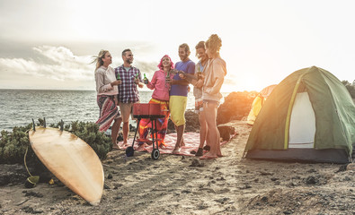 Happy friends drinking beers at camping barbecue picnic next to the ocean - Surfers people having fun and laughing together - Travel, vacation and friendship concept