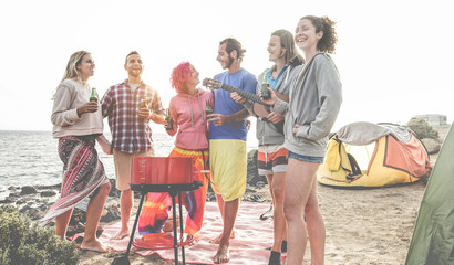 Happy friends drinking beers at camping barbecue picnic next to the ocean - Surfers people having fun and laughing together during summer party holidays - Travel, vacation and friendship concept