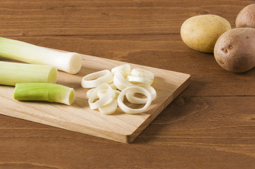 Three potatoes and leeks cut into slices on wooden plank, on wood background.