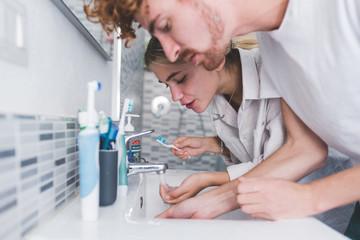 young couple brushing teeth