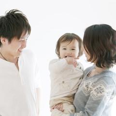 赤ちゃんを抱き微笑む両親