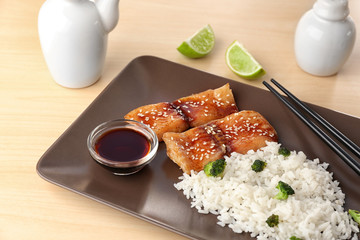 Fish fillet served with rice and soy sauce on plate