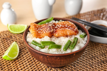 Fish fillet served with rice and green beans on wicker coaster