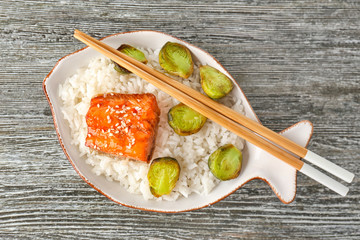 Fish fillet served with rice and brussels sprouts on grey wooden background