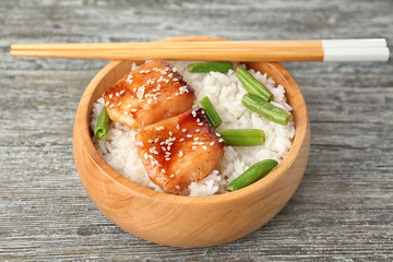 Fish fillet served with rice and green beans in wooden bowl on grey background