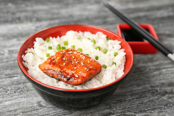 Fish fillet served with rice in bowl on grey background