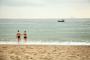 Middle aged couple going into the sea water holding hands.  Caucasian man and woman on a beach from behind. Idyllic seascape with people and boats.