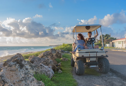 couple driving a golf cart at tropical beach on Isla Mujeres, Mexico
