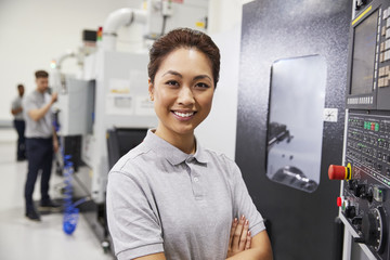 Portrait Of Female Engineer Operating CNC Machinery In Factory
