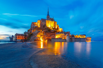 Wall Mural - Famous Mont Saint Michel Illuminated in the evening blue hour with reflection at high tide, Normandy, France