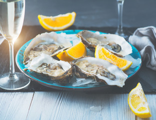 Fresh Oysters closeup on blue plate, served table with oysters, lemon and ice. Healthy sea food. Oyster dinner with champagne in restaurant. Gourmet food